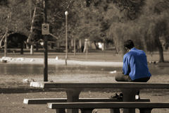 A man feeling blue. Alone on picnic table in the park Royalty Free Stock Photos