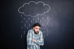 Man feeling cold standing under rain drawn on chalkboard background Stock Photography