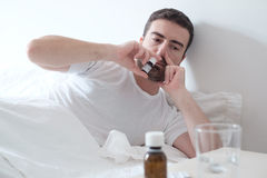 Man feeling cold and using a nasal spray lying in the bed Stock Images