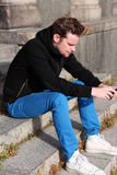 Man feeling depressed sitting down outside Royalty Free Stock Images