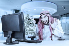 Man feeling excited with money on computer Stock Photography
