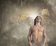 Man feeling lost in the rain. With a ray of hope breaking through the clouds behind him Stock Photos