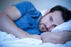 Man feeling sick and sad at night lying in his bed. Man feeling negative emotions trying to sleep at night Stock Images