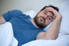 Man feeling sick and sad at night lying in his bed. Man feeling negative emotions trying to sleep at night Stock Photography