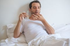 Man feeling sick and taking medicine pills lying in bed Royalty Free Stock Photography