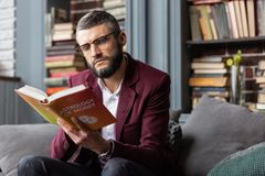 Man feeling thoughtful while reading book about astrology of money stock photography