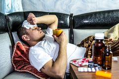 The man feels bad. And is lying under the blanket Royalty Free Stock Images