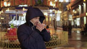 Man feels cold and blows warm air on his hands, tries to warm up. Young handsome man tries to warm up himself. The man is frozen and blows warm air on his hands stock footage