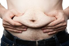 A man feels his fat on his paunch. Closeup Royalty Free Stock Image