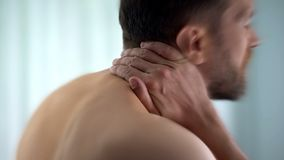 Man feels neck pain after woke up in morning, uncomfortable matrass, closeup stock images