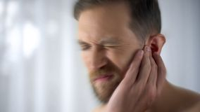 Man feels pain in middle ear, meningitis and hearing loss, inflammation, closeup stock photography