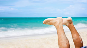Man feet at beach. Pair of a man's feet over the sky on beach Stock Photo