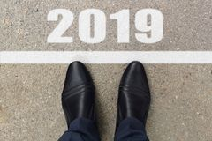 Man feet in black leather shoes standing before text 2019 painted on asphalt, top view royalty free stock photo