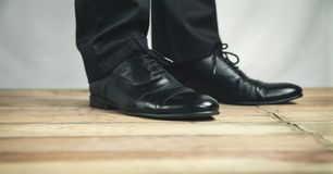 Man feet in black leather shoes stands on wooden floor. royalty free stock photos