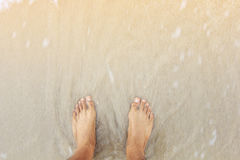 Man feet close-up standing on beach ; emotion of sadness concept. Slow shutter speed Stock Photos