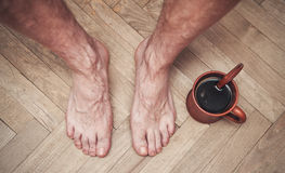 Man feet on floor and cup of coffee Stock Photography