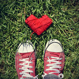 Man feet and heart-shaped coil of red cord on the grass, vignett Stock Photos