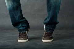 Man feet in jeans. And trainers jumping stock image
