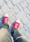 Man feet in red sneakers on cobbled road. Young man feet in red sneakers on cobbled road Royalty Free Stock Photos