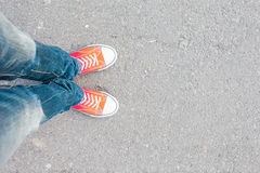 Man feet in red sneakers on cobbled road Royalty Free Stock Images