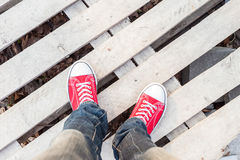 Man feet in red sneakers on cobbled road. Young man feet in red sneakers on cobbled road Stock Photo