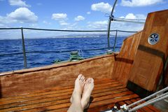 Man feet relax on golden wooden old sailboat. Blue sea summer vacation dream stock photography