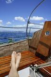 Man feet relax on golden wooden old sailboat Stock Image