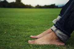 Man feet relaxing on grass enjoying in a day in a park with sky background, Thailand Royalty Free Stock Image
