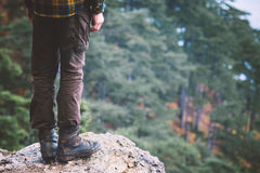 Man Feet on rocky cliff edge with forest aerial view Stock Photos