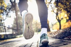 Man feet run. From back. Close up. Man feet run. From back. Young sporty man jogging trough park Stock Photography