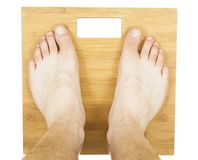 Man feet on the scale. Isolated on white stock photo