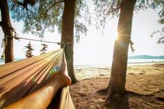 Man feet sleeping on swing. At the sunset beach background Stock Photo