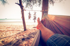 Man feet sleeping on swing. At the sunset beach background Royalty Free Stock Image