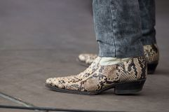 Man feet with snake american boots at country show in outdoor. Closeup of man feet with snake american boots at country show in outdoor stock photo