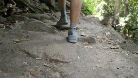 Man feet in sneakers and socks trek along steep stone climb
