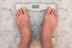 Man feet standing on weight scale stock images