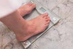 Man feet standing on weight scale stock photography