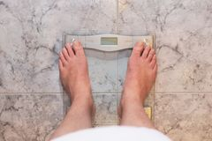 Man feet standing on weight scale royalty free stock photography
