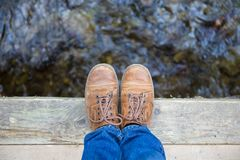 Man standing at rivers edge. Man feet standing on wooden bridge edge over mountain river travel lifestyle concept summer vacations Royalty Free Stock Images