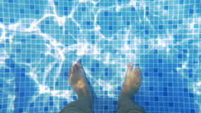 Man Feet in Sunlit Swimming Pool. Slow motion shot of feet of man standing in the swimming pool, there are sunlight flecks in the water stock video