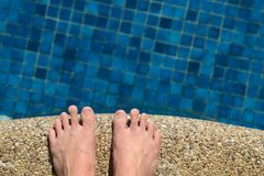 Man feet at swimming pool. Close up of man feet at the border front of swimming pool Stock Images