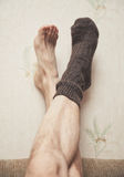 Man feet up on the wall in woolen sock Royalty Free Stock Photography