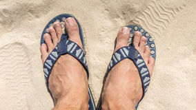 Man feet wearing flip flops on a beach Royalty Free Stock Image