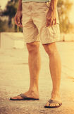 Man Feet wearing shorts and flip flops standing Outdoor summer. Vacations lifestyle concept Royalty Free Stock Images