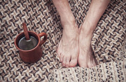 Man feet on woolen plaid and cup of coffee Royalty Free Stock Photos
