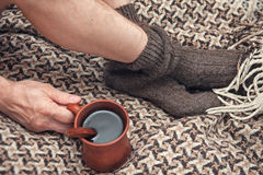 Man feet on woolen plaid and cup of coffee Royalty Free Stock Photography