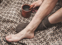 Man feet on woolen plaid and cup of coffee Royalty Free Stock Images