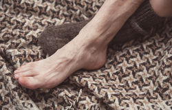 Man feet on woolen plaid in woolen sock. Cozy concept Royalty Free Stock Photo