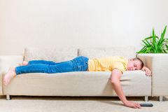 Man fell asleep on the couch after watching TV Stock Photo