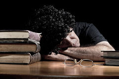 Man fell asleep while reading books. In dark room Stock Photography